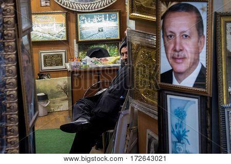 ISTANBUL TURKEY - DECEMBER 29 2015: Shopkeeper selling a huge portrait of the Turkish President Recep Tayyip Erdogan