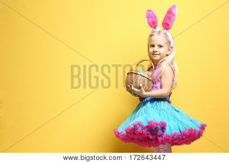 Cute little girl with bunny ears and basket full of Easter eggs on color background