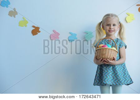 Cute little girl with basket full of Easter eggs at home