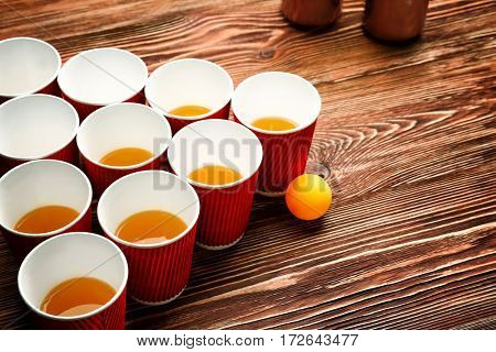 Plastic beer pong cups and ball on wooden table