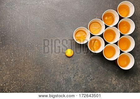 Plastic beer pong cups and ball, top view