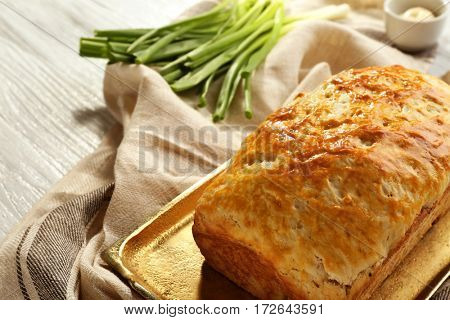 Copper tray with tasty loaf of beer bread on wooden table