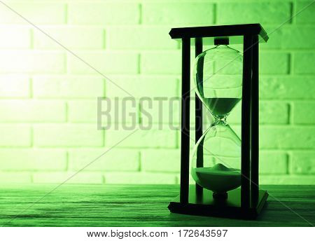 Hourglass on brick wall background