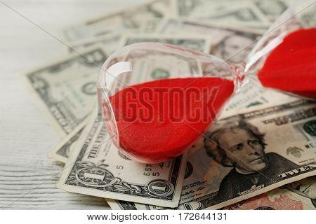 Dollar banknotes and sandglass, closeup