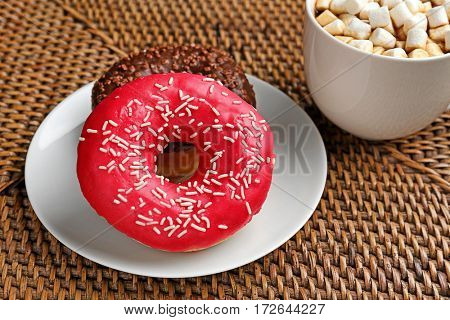 Tasty donuts with cup of coffee on table