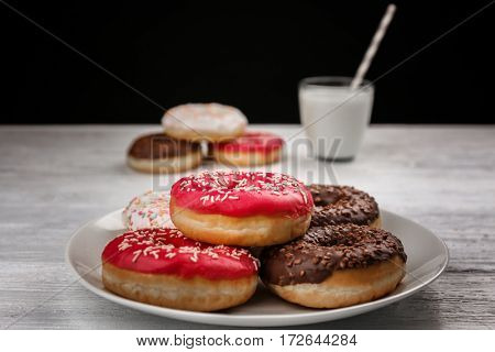 Tasty donuts with cup of milk on table