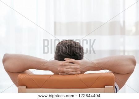 Rear view of relaxed man with hands behind his head sitting on chair in light room