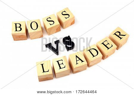 Wooden cubes and black letters forming text BOSS VS LEADER isolated on white