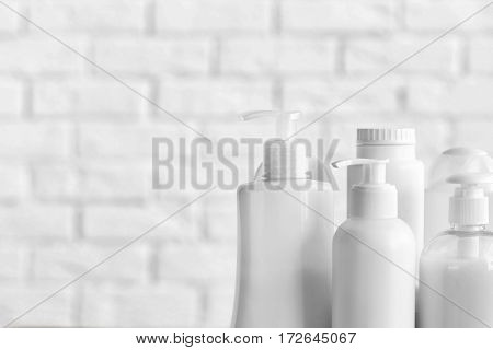 Plastic bottles of baby cosmetic products on white brick wall background