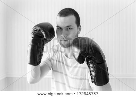 horizontal black and white image of a young caucasian man wearing boxing gloves in a fighting stance with one glove in focus and the rest of image slightly blurred and room for text.