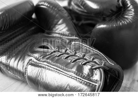 horizontal close up black and white image of a pair of boxing gloves filling the whole image.