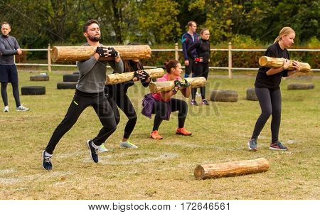 Kiev Ukraine - October 08. 2016. Street workout CrossFit training. Man and woman performing the long jump with a log on his hands.