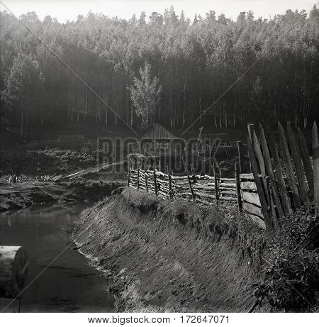 Old Fence On The Edge Of The Ravine With A Wooden House On The Woodside