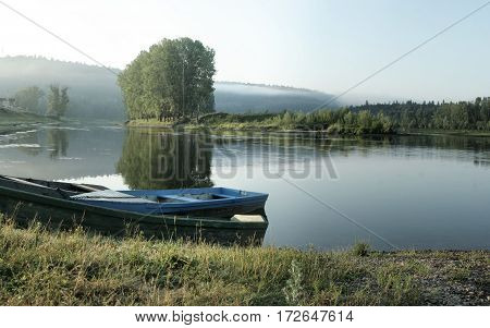 Three Boats On The Shore In A Quiet Backwater