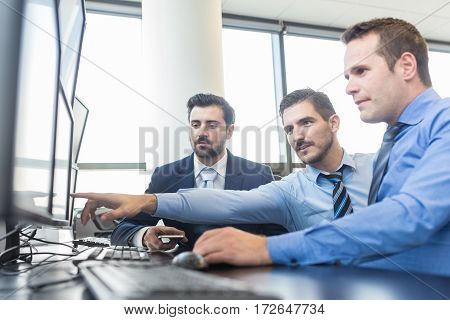 Business team working in corporate office. Businessman pointing on screen. Stock traders looking at graphs, indexes and numbers on multiple computer screens. Business success concept.