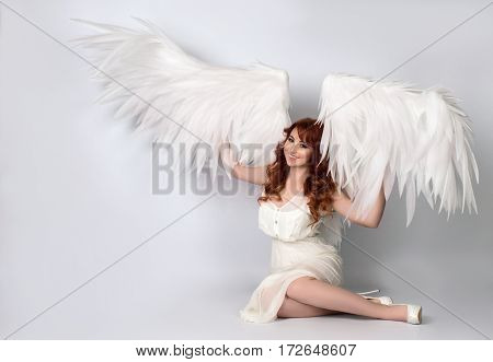 model with open angel wings sitting in studio white background