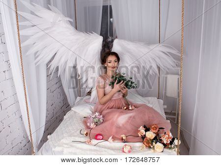 beautiful young model with open angel wings and pink dress sitting on hanging bed suspended from the ceiling . Bed is decorated with flowers. White loft interior.