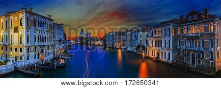 Panoramic view of  Gondolas on Canal Grande with historic Basilica di Santa Maria della Salute in the background at sunset in Venice, Italy