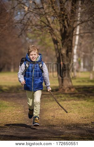 Happy schoolboy with his school bag on his shoulders running on a sunny day. Child going home from school. Cute boy rushing.
