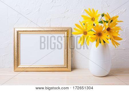 Landscape golden frame mockup with yellow rosinweed flowers. Empty frame mock up for presentation artwork.