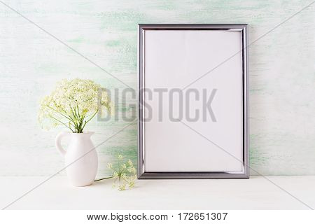 Silver frame mockup with delicate wild field flowers in pitcher. Empty frame mock up for presentation artwork.