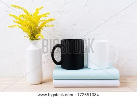 White and black mug mockup with ornamental yellow flowering grass. Empty mug mock up for design promotion.
