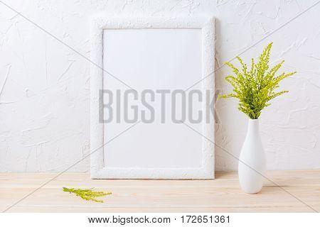 White frame mockup with ornamental grass in exquisite vase. Empty frame mock up for presentation design