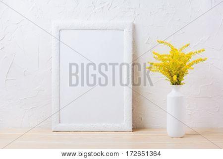White frame mockup with ornamental yellow flowering grass in vase. Empty frame mock up for presentation design.