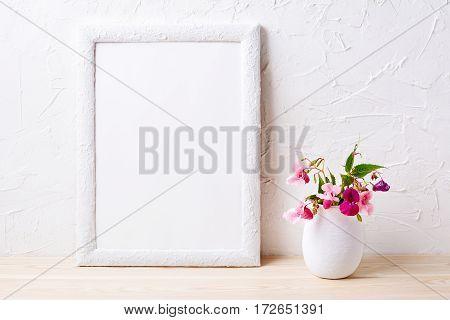 White frame mockup with pink flowers in flowerpot. Empty frame mock up for presentation design.