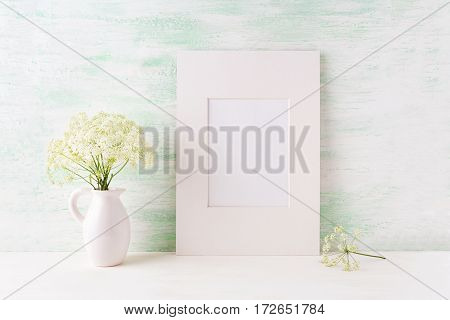 Easy white frame mockup with tender wild flowers in pitcher. Empty frame mock up for presentation artwork.