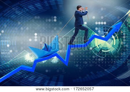 Businessman pulling boat over line chart
