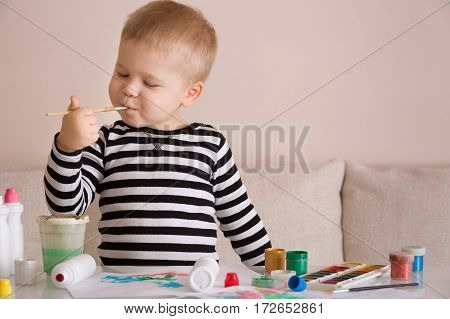 Portrait of cute toddler boy drawing at home with colorful paints and brush. Creative child having fun. Educational concept