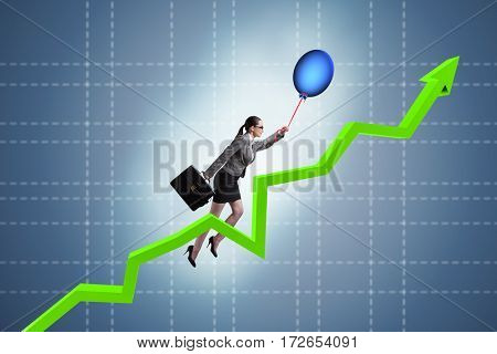 Businesswoman flying on hot balloon over graph