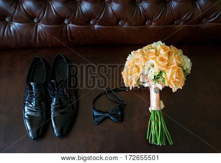 wedding bouquet with groom's shoes and bow tie lying on chair near window.
