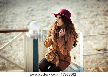 A portrait of a Long-haired stylish young girl in a hat and long ginger winter coat smiling as walking in the coast beach