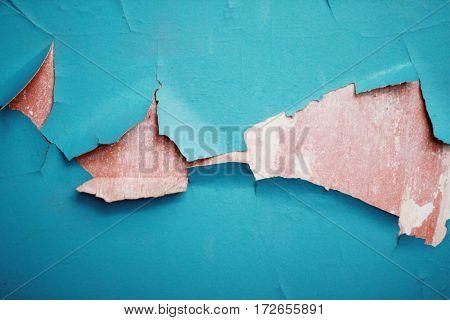 Blue paint on an exterior wall cracked and flaking to reveal old concrete beneath