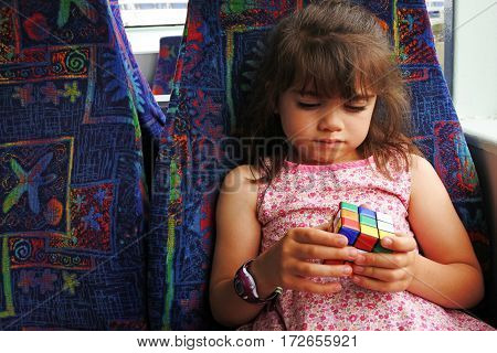 AUCKLAND - DEC 12 2016:Young girl plays with Rubik's Cube.Over 350 million cubes sold worldwide making it the world's top-selling puzzle game and the world's best-selling toy.