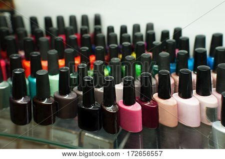 Set of different nail varnishes on shelves in cosmetic beauty saloon
