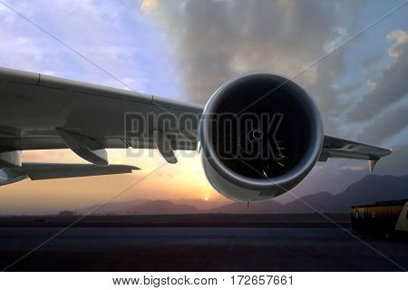 Commercial airplane turbine engine on runway during sunset