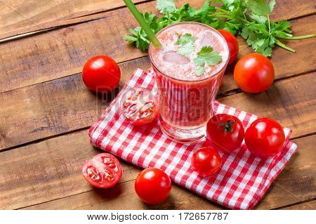 Glass of tomato smoothie or juice, fresh tomatoes and cilantro on wooden dark background