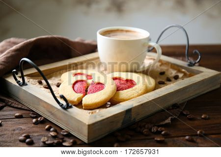 Heart shaped cookies with cup of coffee on tray, closeup