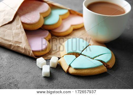 Heart shaped cookies with cup of coffee and parchment on grey background, closeup