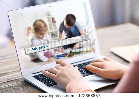 Adoption concept. Female hands with laptop and search box on screen
