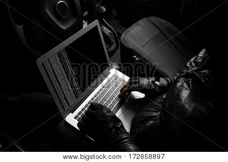 Thief hacking car security system with laptop