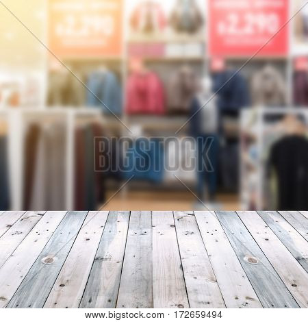 Empty table and blurred cloth store with bokeh background for product display.
