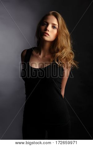 Beautiful girl with long wavy and shiny hair . Blonde woman with curly hairstyle