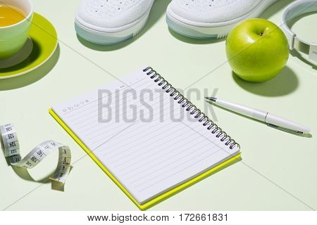 Fitness Plan Concept. Sneakers, Tea, Apple And Headphone On Pastel Color Background With Open Notebo