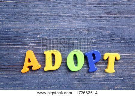 Word ADOPT on color wooden background