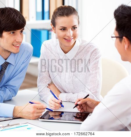 Young couple discussing terms of the loan with the bank manager