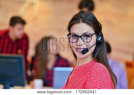 Portrait of happy smiling female customer support phone operator at workplace